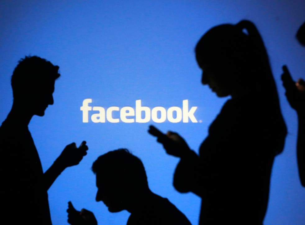 People are silhouetted as they pose with mobile devices in front of a screen projected with a Facebook logo, in this picture illustration taken in Zenica October 29, 2014