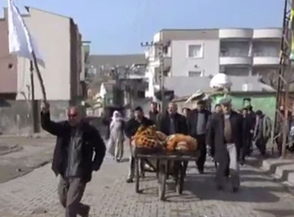 In the video, several civilians are shown waving white flags as they walk with a cart which appears to hold two covered bodies