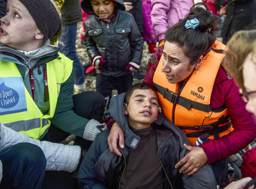 A mother hugs her boy after arriving on the Greek island of Lesbos along with other migrants and refugees
