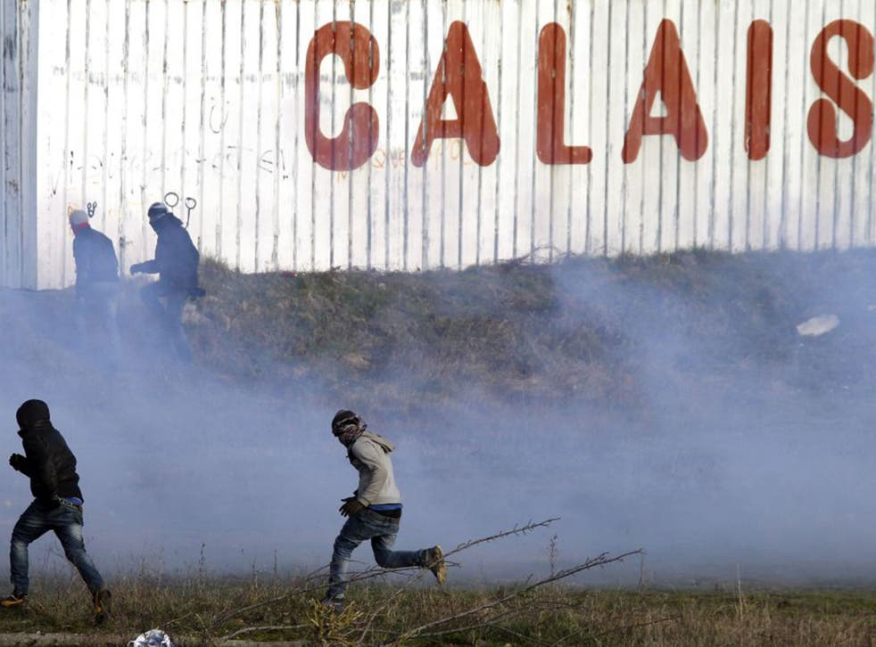 Migrants run away from tear gas thrown by police forces near the Channel Tunnel in Calais