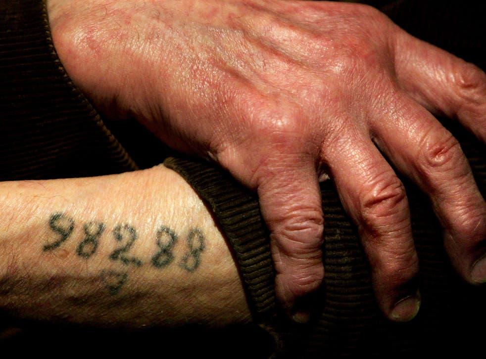 Auschwitz survivor Mr. Leon Greenman, prison number 98288, displays his number tattoo on 9 December, 2004, at the Jewish Museum in London