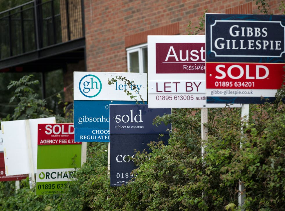 A row of estate agent boards are placed outside sold and let properties