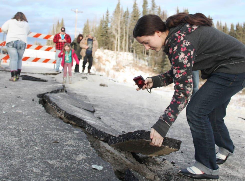 Tyrrel Corveia, 14, lifts a piece of the road surface along a crack in Kalifornsky-Beach Road near Kasilof, Alaska, Sunday, Jan 24, 2016
