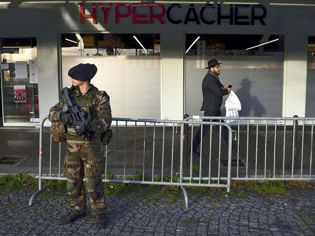 A Jewish man walks past a French soldier standing guard outside the Hypercacher kosher supermarket where four Jewish people were murdered by Islamist gunmen last January