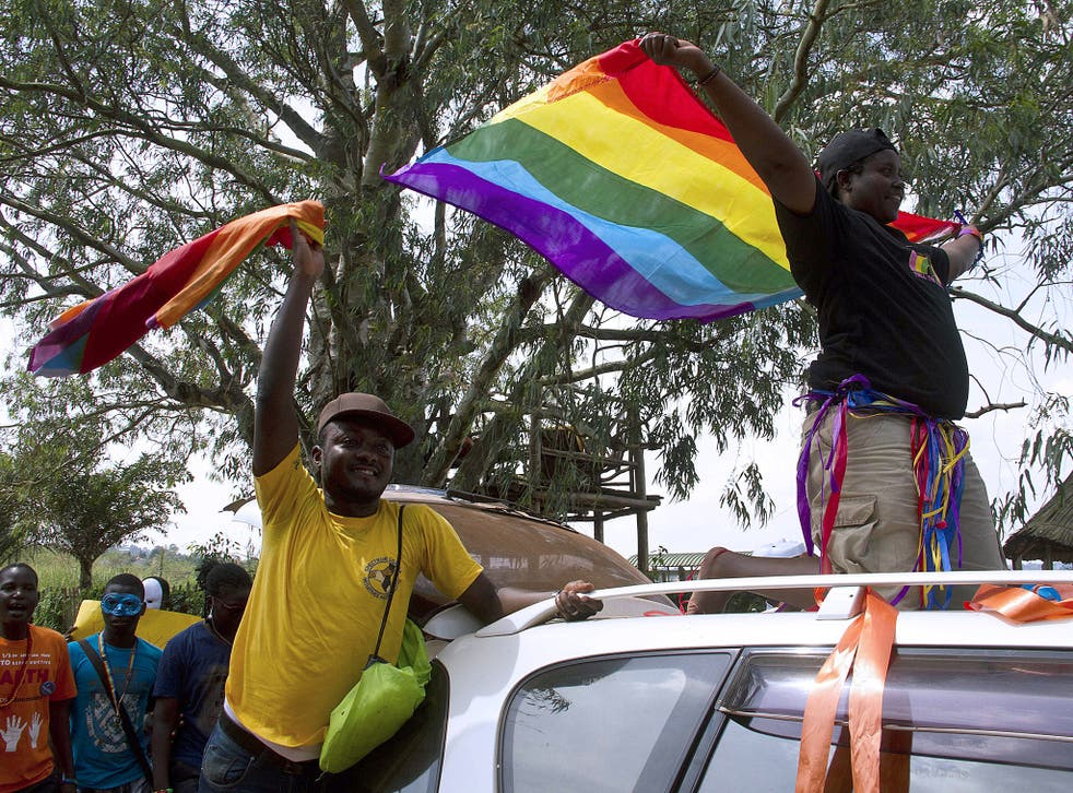 People wave rainbow flag during the the first gay pride rally since the overturning of a tough anti-homosexuality law in Entebbe, Uganda
