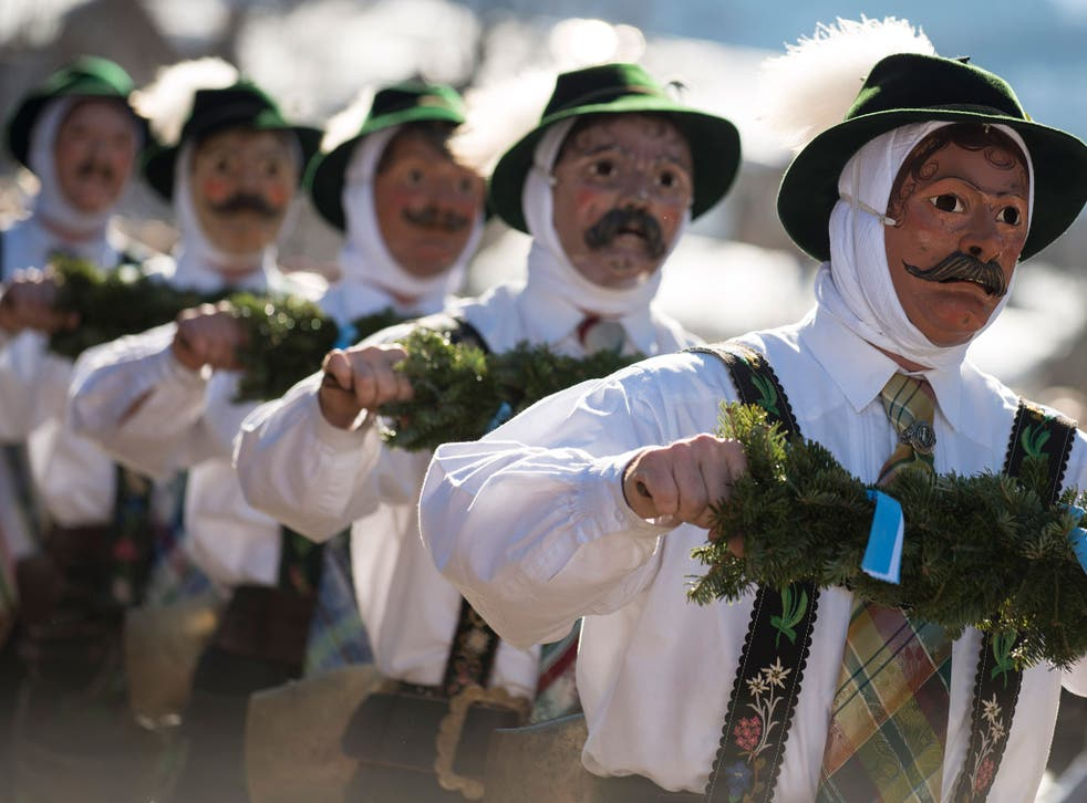 Costumed participants wearing traditional wooden masks perform in the annual carnival parade on February 12, 2015 in Mittenwald