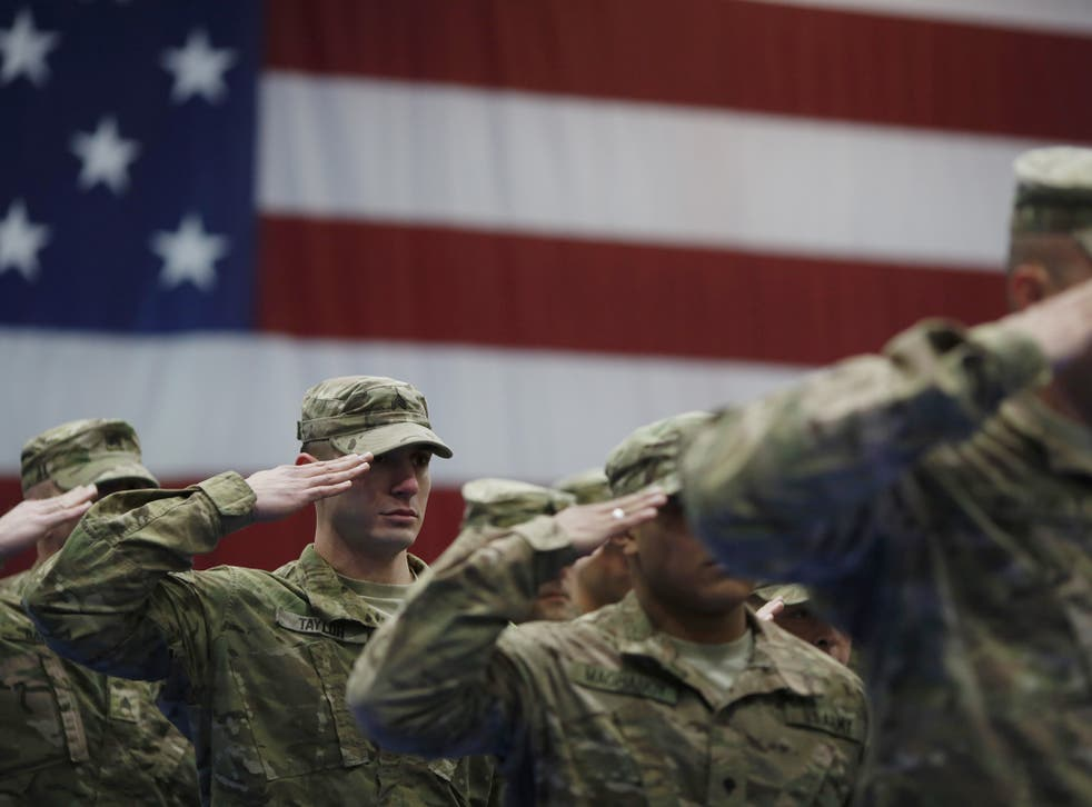 Soldiers salute during the playing of the Star Spangled Banner during a homecoming ceremony at Fort Knox, Kentucky