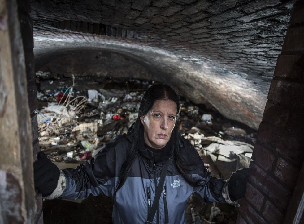 Angela Penny Barratt who works for Street Support Salford pictured in the cave in an enclosed archway near Manchester Cathedral.