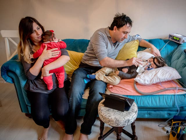 Serdar Agirman tending at home to his two-year-old son, Ruzgar, who has spinal muscular atrophy, alongside his wife Pelin and their baby daughter, Karia