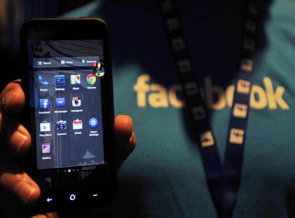 A Facebook employee holds an HTC phone running the social network's ill-fated 'Home' mobile operating system in 2013