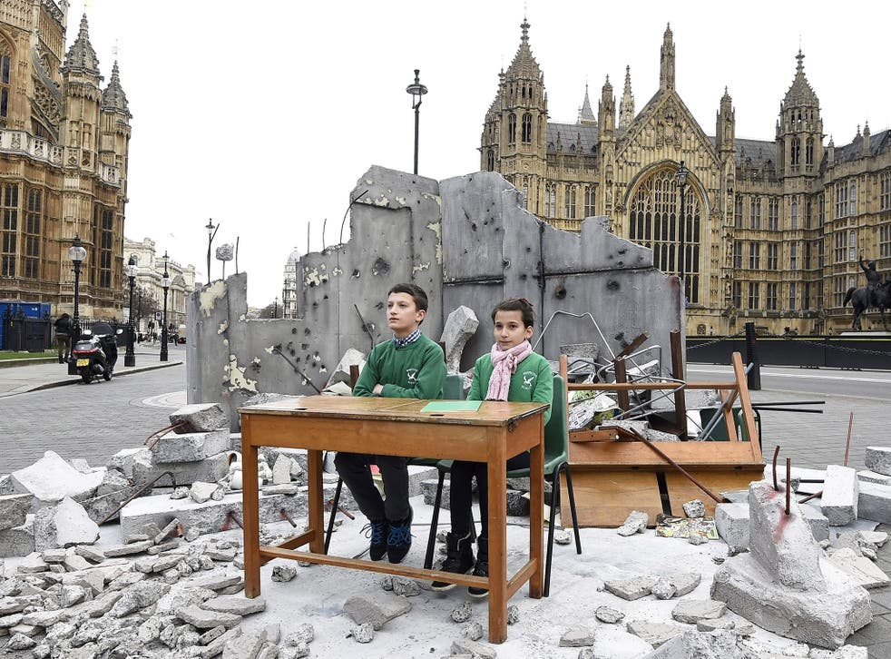 Abdallah, 12, and Dania, 10, whose school was bombed in Aleppo, sit in a mock up of a destroyed classroom, outside the Houses of Parliament in London