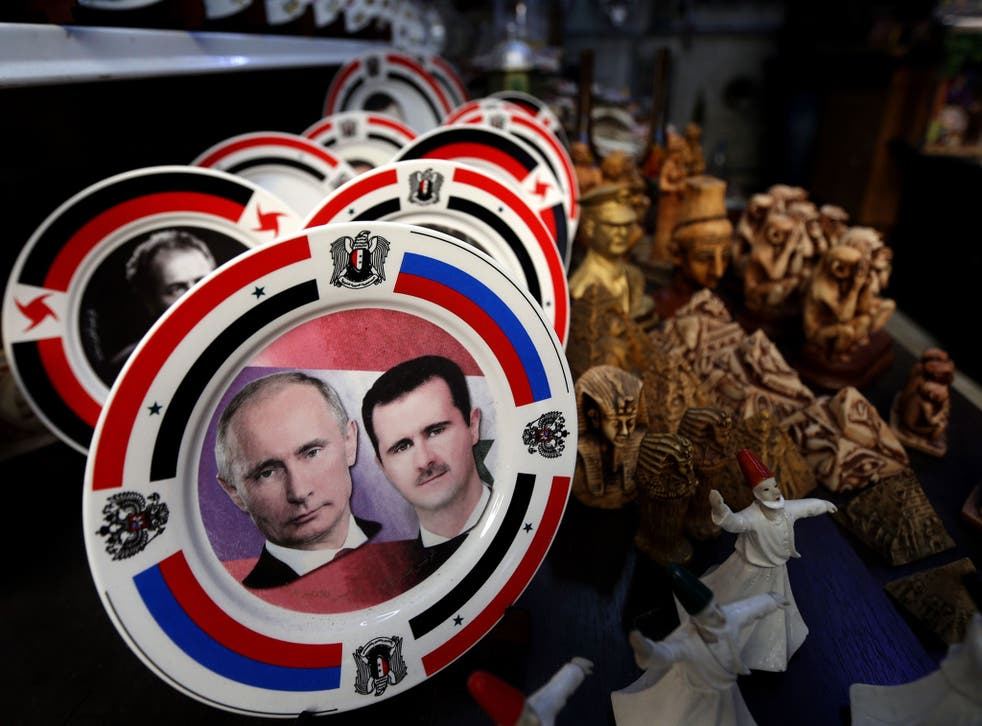 Porcelain plates bearing portraits of Syrian President Bashar al-Assad, right, and his Russian counterpart Vladimir Putin, left, are displayed at a handicrafts shop in the Syrian capital, Damascus
