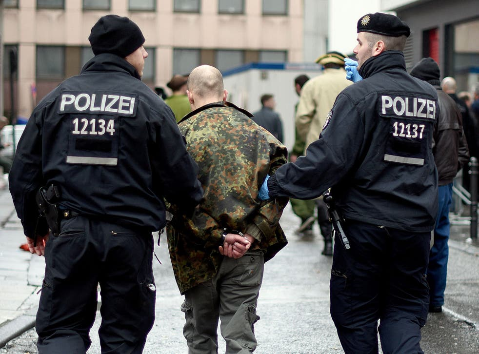 Police detain a man during the celebrations in Cologne