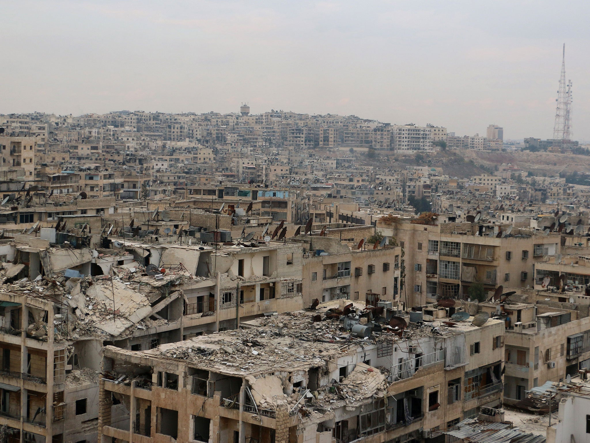 (Damaged buildings in the rebel-held Ansari district of the northern Syrian city of Aleppo, 24 November, 2014 © Baraa Al-Halabi/AFP/Getty Images)