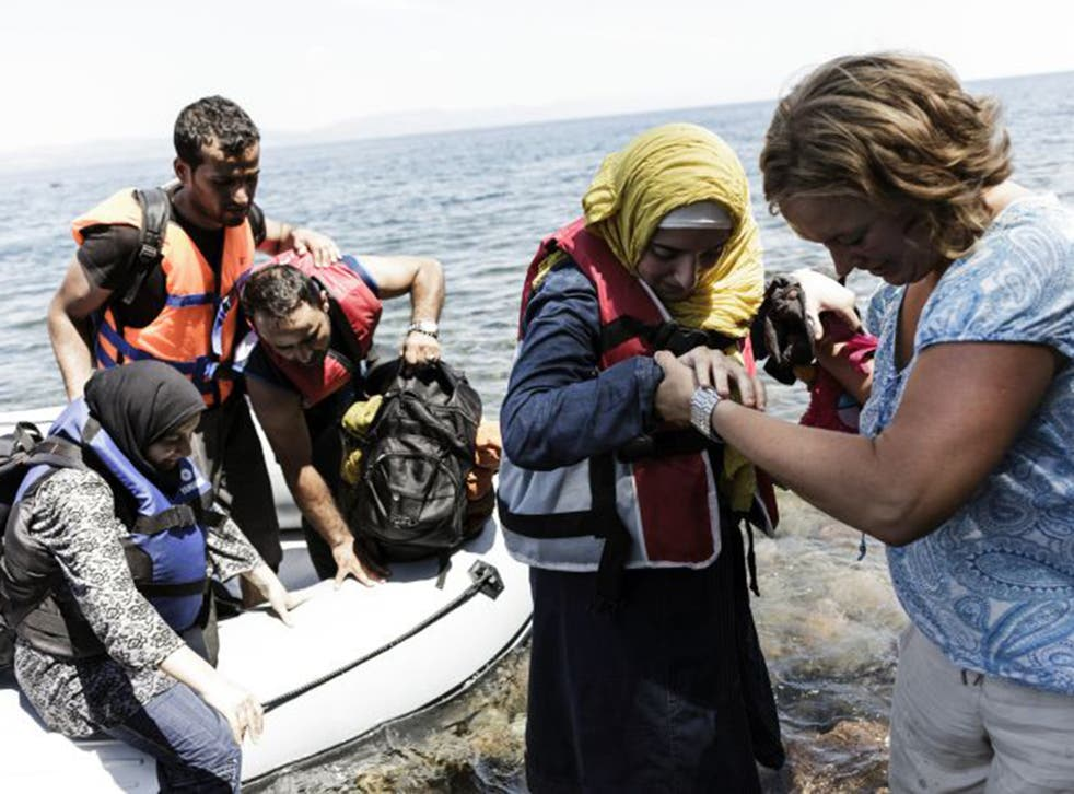 Syrian people arrive on the Greek island of Lesbos after crossing the Aegean sea from Turkey to Greece