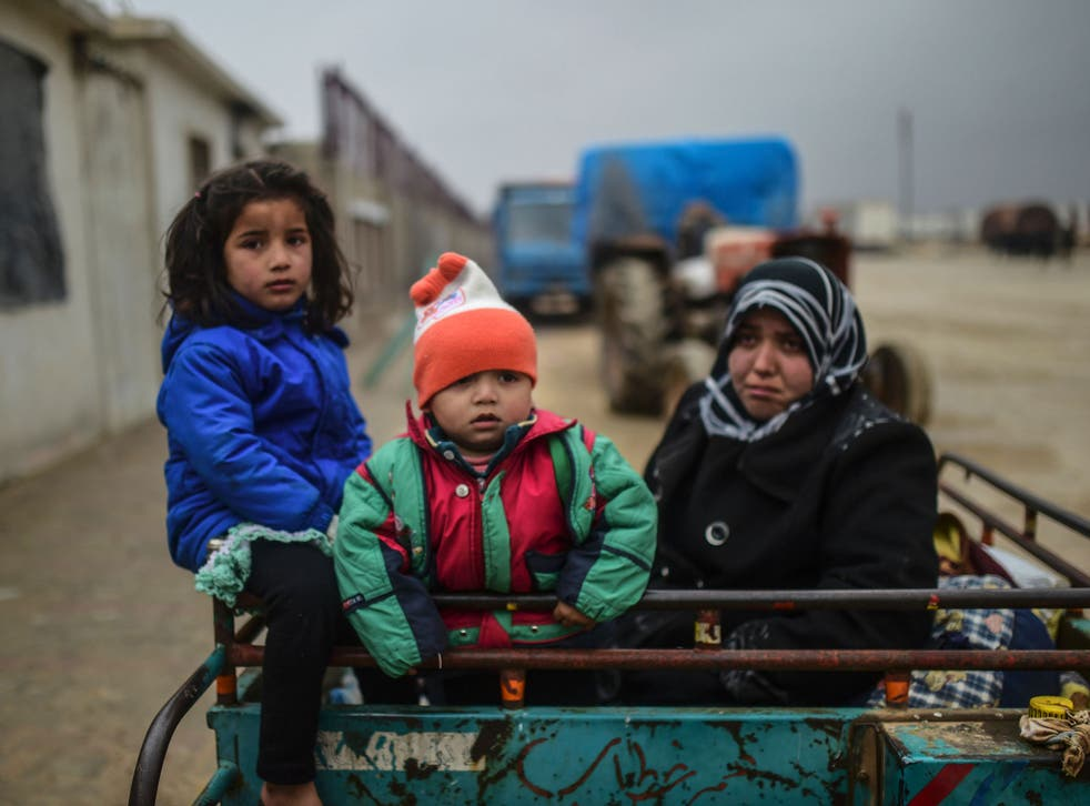 A refugee family, fleeing airstrikes in Aleppo, arrive at the Turkish border crossing of Bab-al Salam