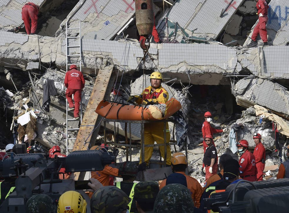 A rescue worker carries a victim from the building