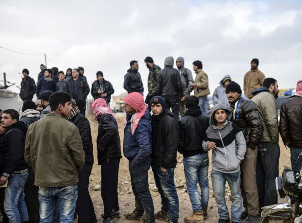 Syrian refugees wait for tents after fleeing the Russian-backed regime attack on the northern city of Aleppo
