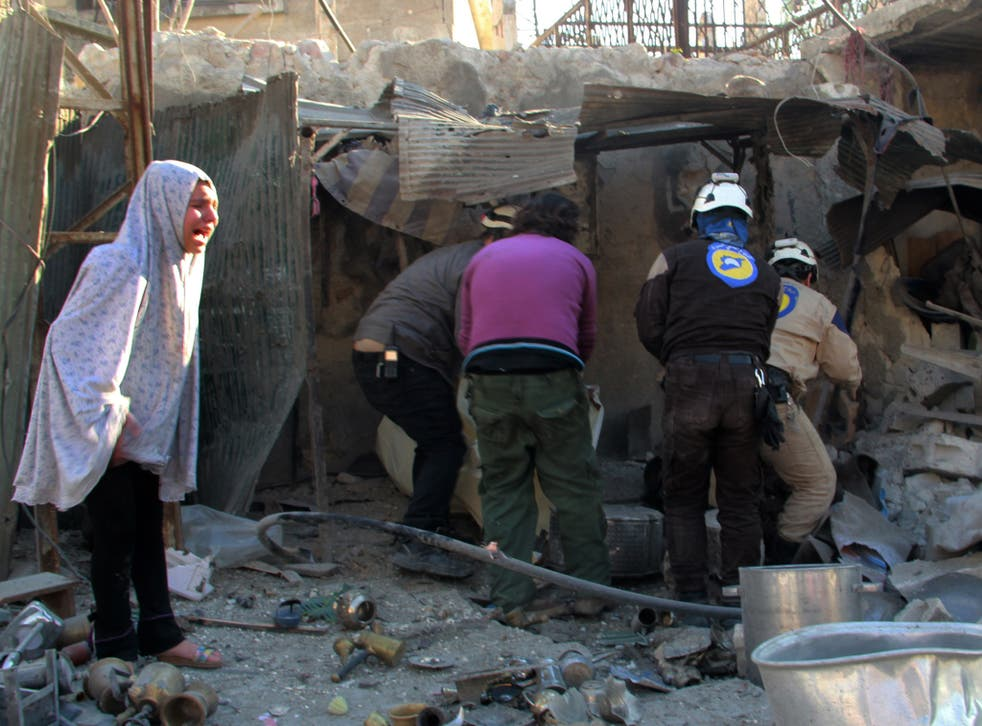 A Syrian girl whose home was destroyed by Russian airstrikes on Aleppo watches as workers attempt to clear away the rubble to look for survivors