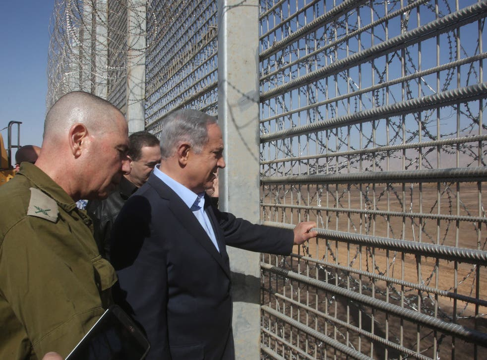 Israeli Prime Minister Benjamin Netanyahu (C) tours along the new fence at the border between Jordan and Israel near the city of Eilat,southern Israel