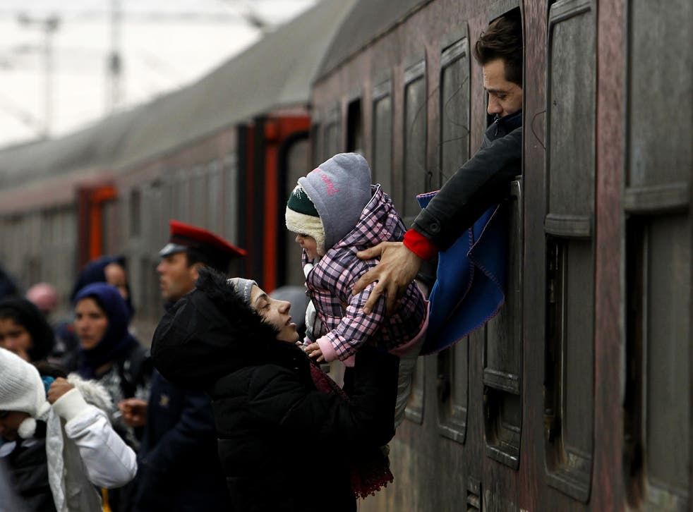 A refugee man passes a baby to a woman from a train window, upon their arrival at the transit center for refugees near northern Macedonian village of Tabanovce