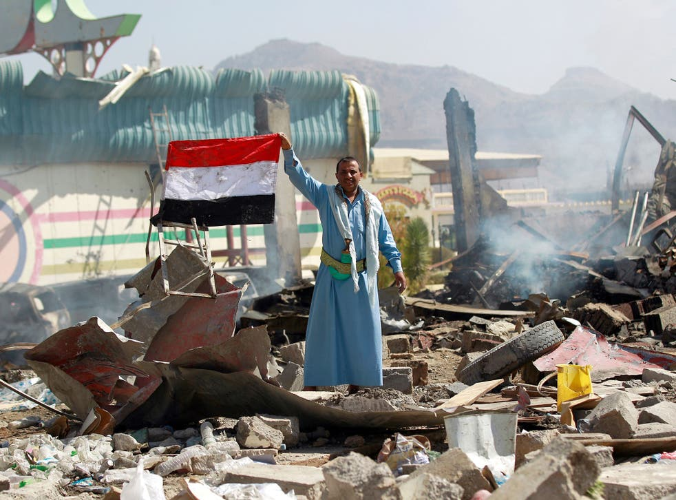 A Yemeni man waves his national flag as he stands amid the ruins of a school and a bowling club hit by an air-strike carried out by the Saudi-led coalition, in the capital Sanaa,