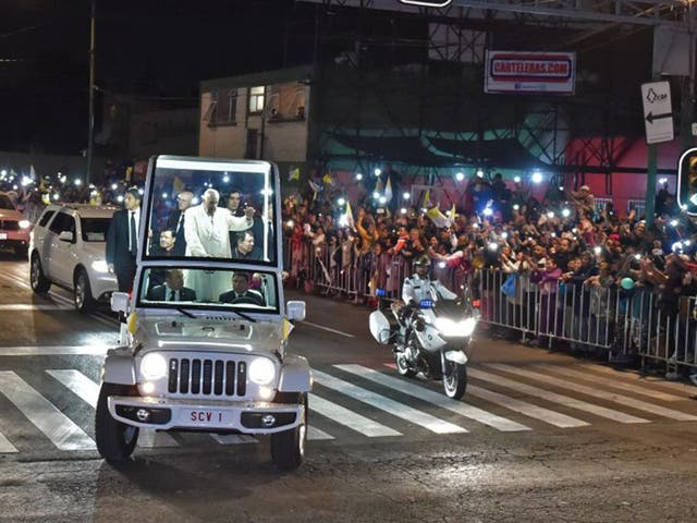 Pope Francis waves from his Popemobile as citizens flock to greet him in Mexico City