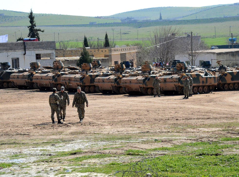 Turkish Army vehicles and tanks wait near the Syrian border