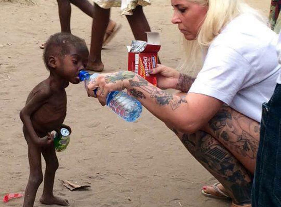 Anja Ringgren Loven gives water to Hope, 2, after finding the emaciated boy wandering the streets