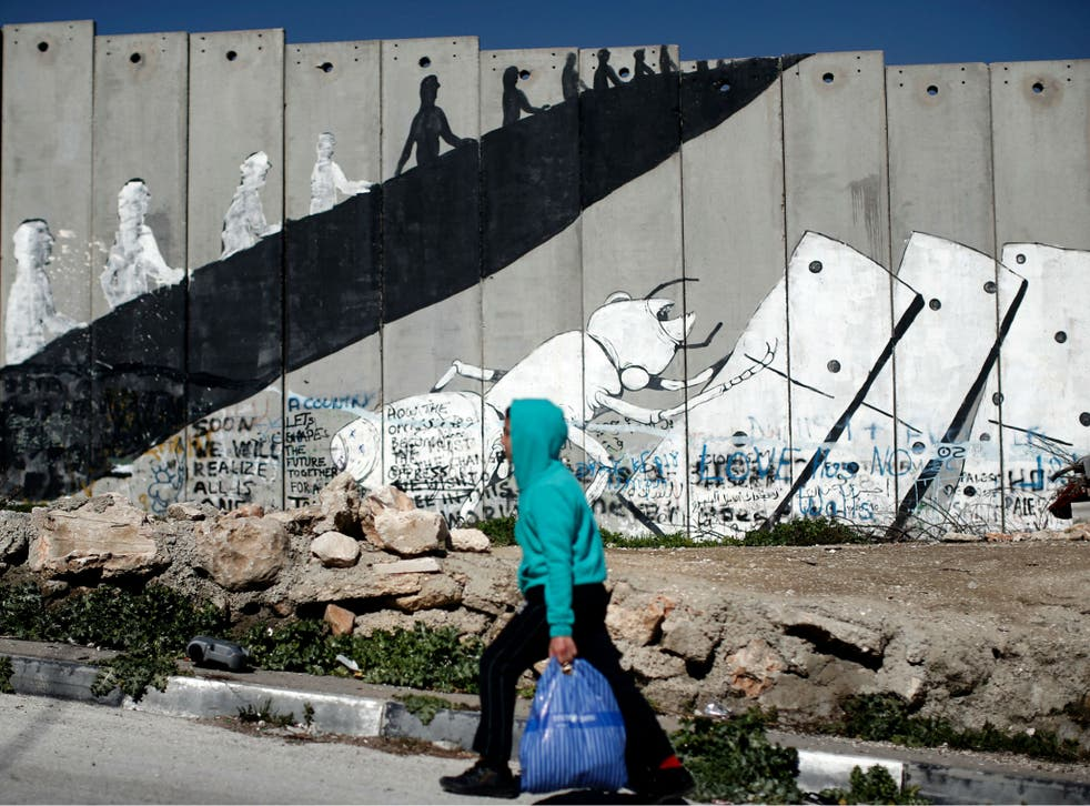 A Palestinian boy walks past graffiti painted on Israel's controversial separation barrier in the Aida refugee camp situated inside the West Bank town of Bethlehem, on February 12, 2016