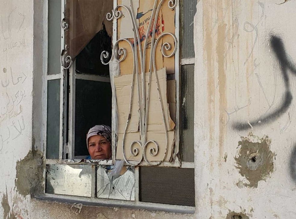 A woman peers out of her window in the battered district of Damascus where a fragile ceasefire holds