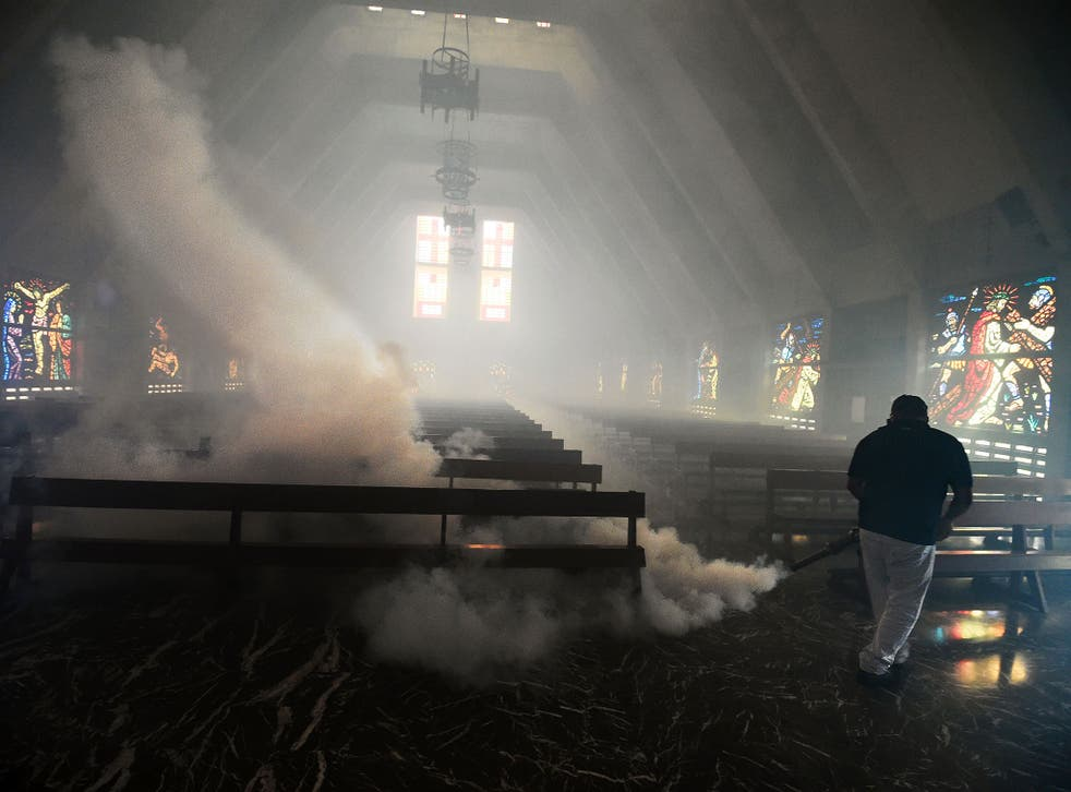 A Health Ministry employee fumigates against the Aedes Aegypti mosquito inside a church in Caracas on 5 February, 2016