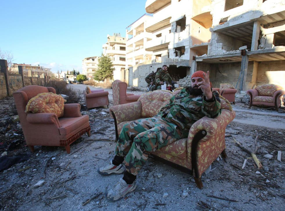 A government soldier relaxes after the recapture of Salma from IS