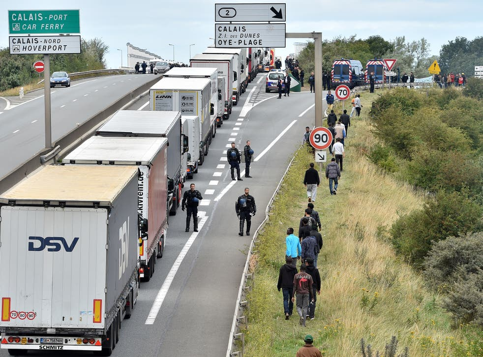 Police officers try to prevent migrants from climbing aboard trucks travelling to Britain, outside Calais last year