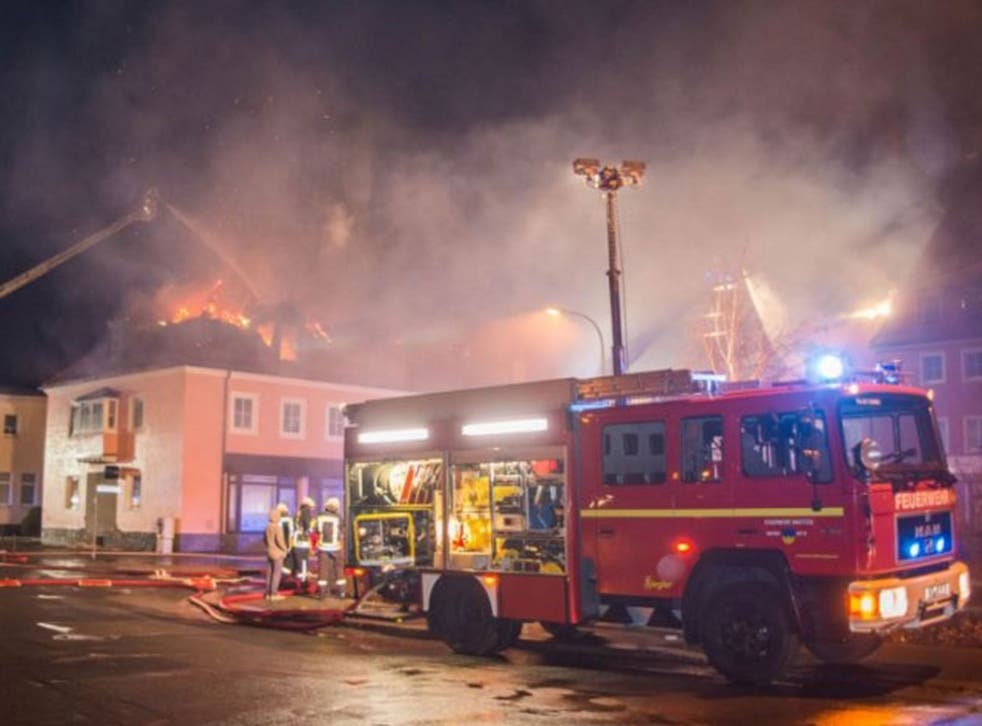 Firefighters tackle a blaze at a refugee shelter in Bautzen, Germany