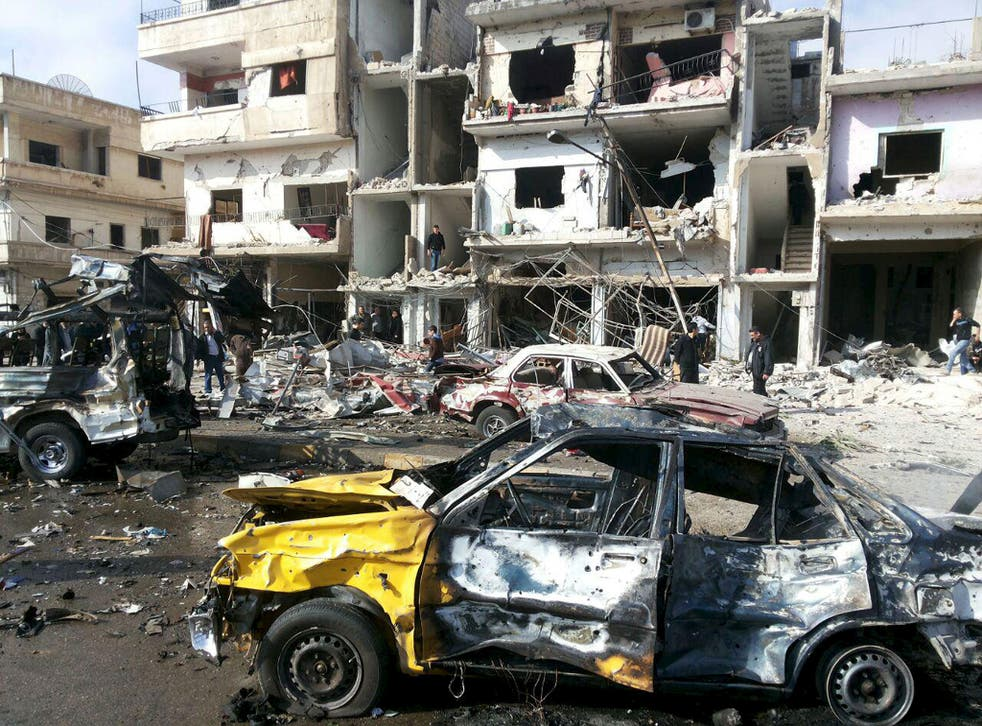 People inspect the site of a two bomb blasts in the government-controlled city of Homs, Syria, on 21 February, 2016