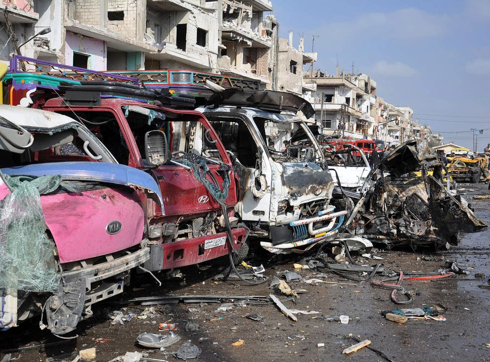 Wrecked buildings and vehicles at the site of twin car bombings that killed at least 57 people in the Syrian city of Homs
