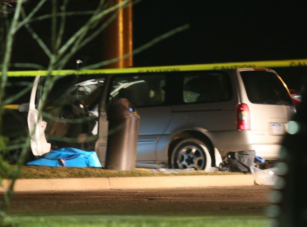 Police investigate the scene of one of the shooting scenes in Kalamazoo