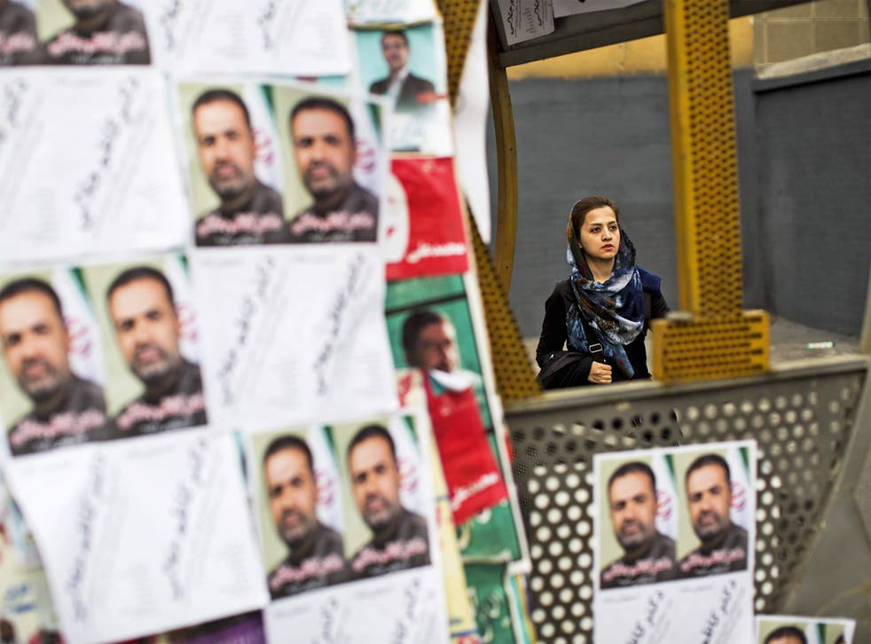 A woman walks past electoral posters for the upcoming elections in Tehran