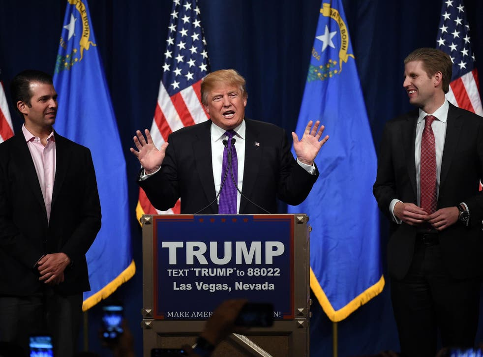 Trump speaks as his sons Donald Trump Jr. (L) and Eric Trump (R) look on during a caucus night watch party
