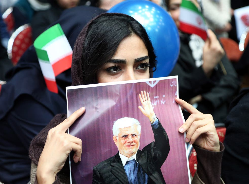 An Iranian woman holds up a poster of Mohammad Reza Aref, a prominent reformist candidate