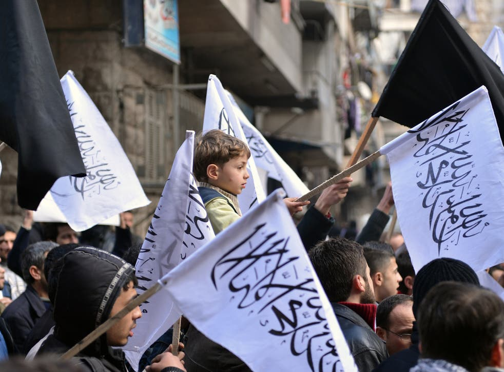 Syrian supporters of the Al-Nusra group wave flags as they march during an anti-regime demonstration