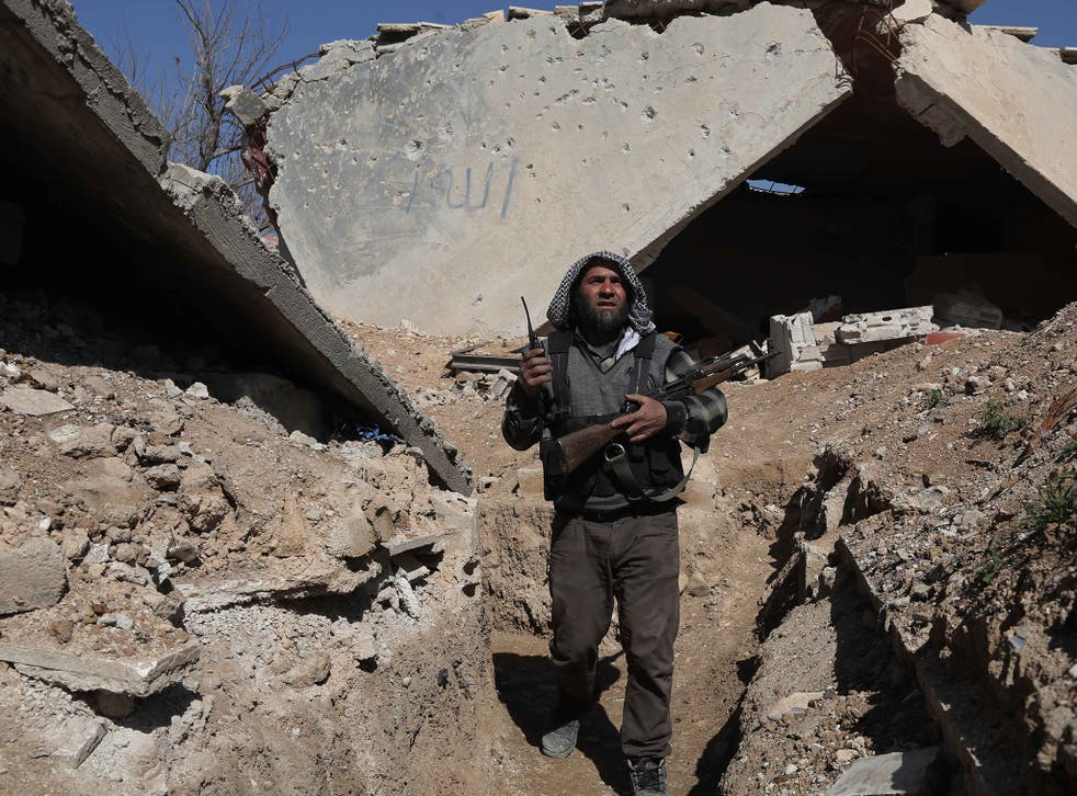 A rebel fighter on guard in the town of Arbin in the eastern Ghouta region near Damascus