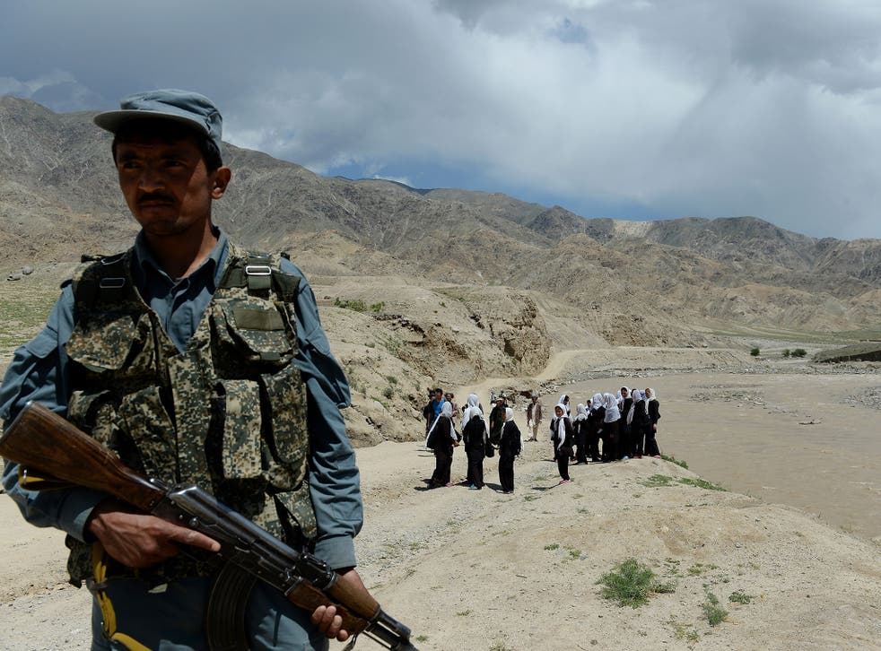 An Afghan policeman stands guard as schoolgirls wait for a bus in Baghlan province