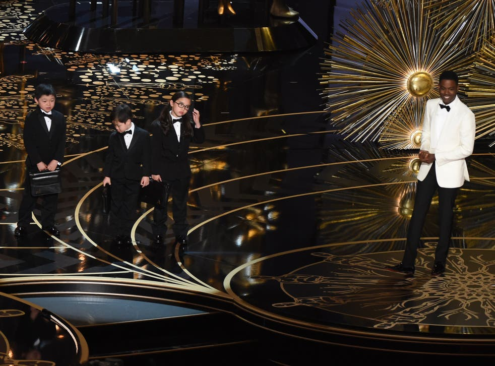 Actor Chris Rock presents children representing accountants from PricewaterhouseCoopers on stage at the  Oscars