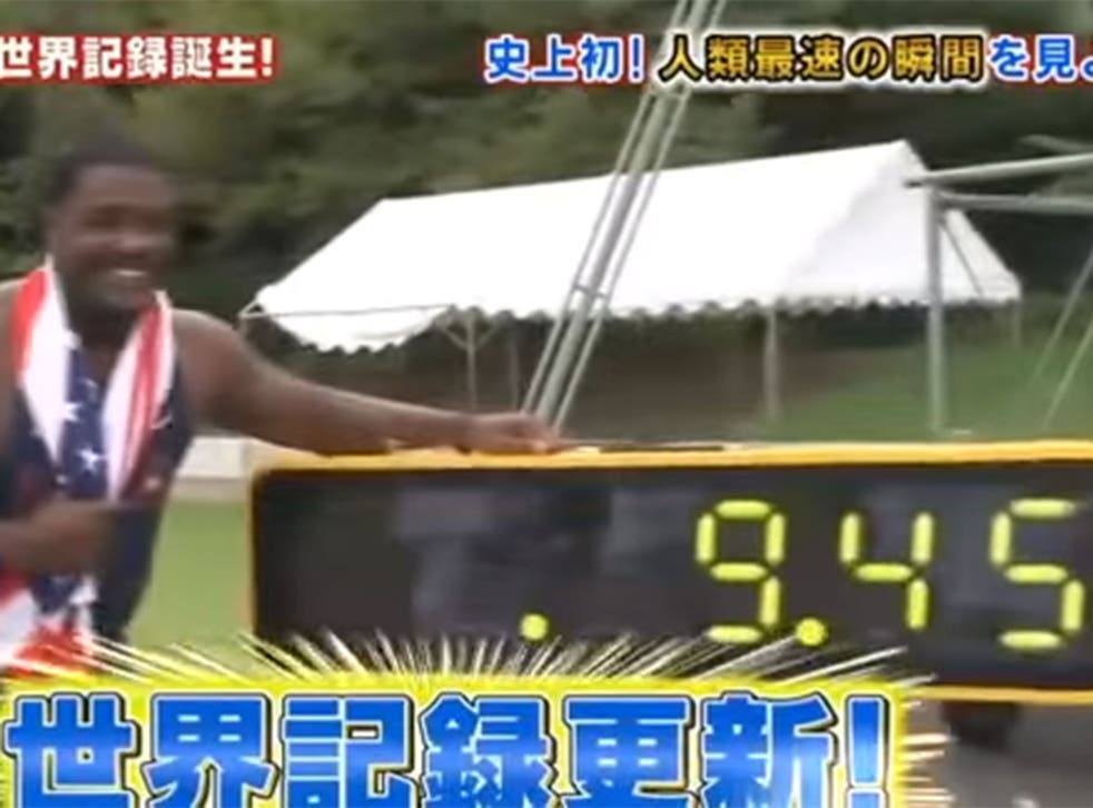 Justin Gatlin poses next to the time