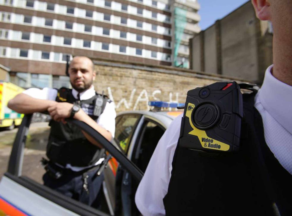 Watching the watchmen: Metropolitan Police Constable Yasa Amerat and a colleague show off body-worn video (BWV) cameras