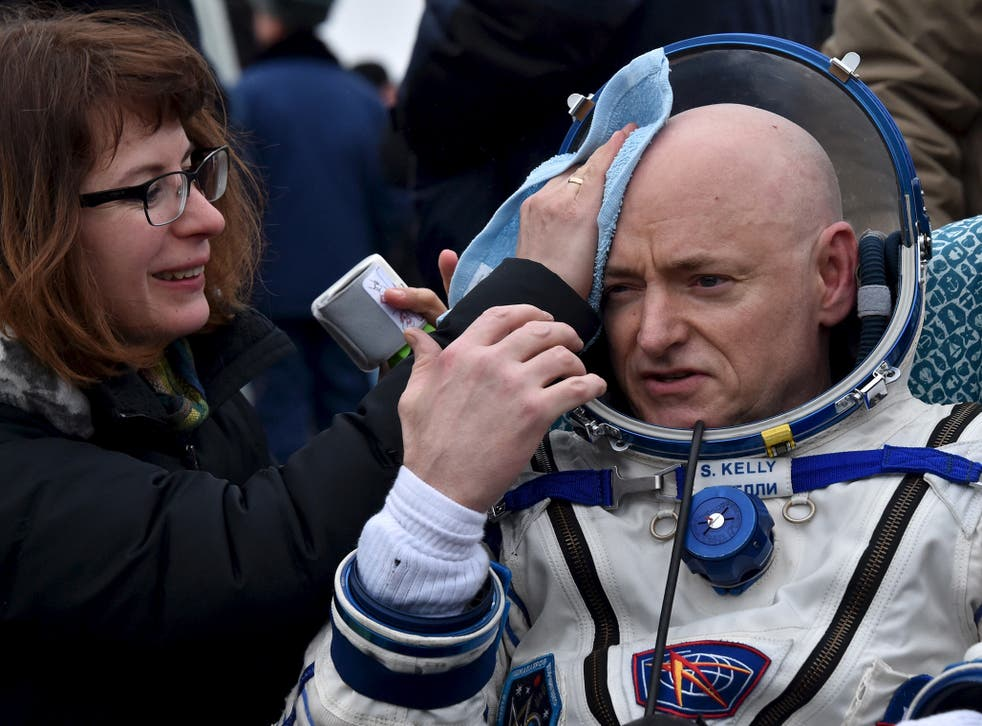 U.S. astronaut Scott Kelly is assisted by ground personnel shortly after landing near the town of Dzhezkazgan