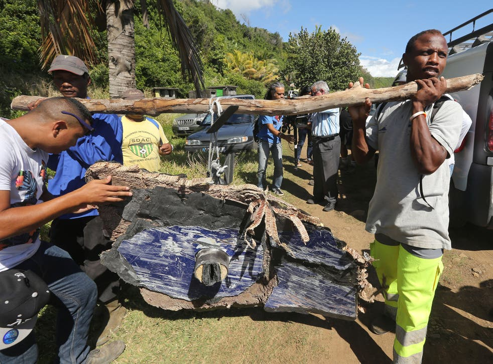 Local ecological association members and volunteers carry debris found on France's Reunion Island, last August