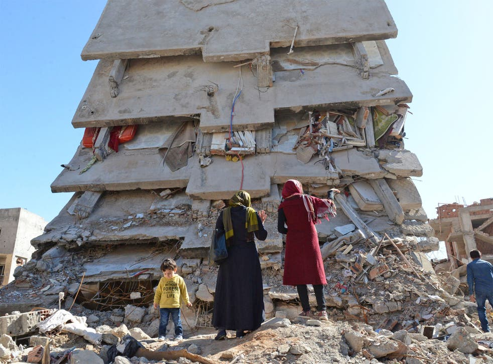 A family stands among the rubble of damaged buildings following heavy fighting in Cizre